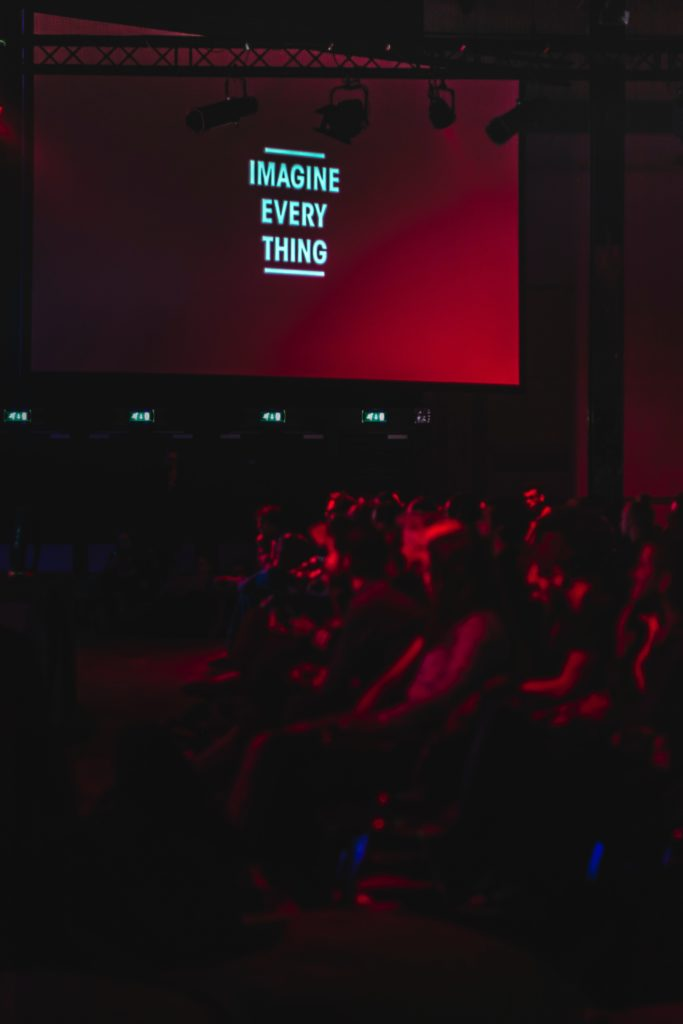 "Dark room filled with people at a company event. Text on screen saying ""imagine everything""."